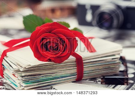 Stack of postcard and photograph tied with velvet ribbon and red rose film and vintage camera.