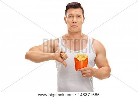 Disappointed man holding a bag of fries and making a thumb down sign isolated on white background