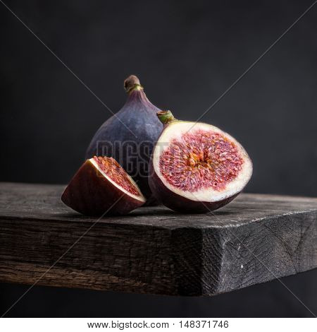 Sliced ripe figs on a wooden table. Black background