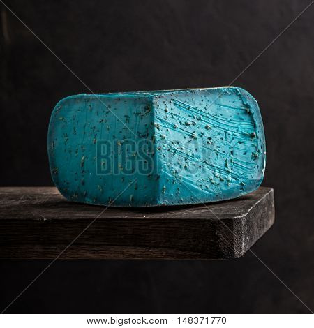 blue cheese on a wooden board. Black background