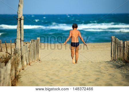 Happy little boy running around at the beach, enjoying himself