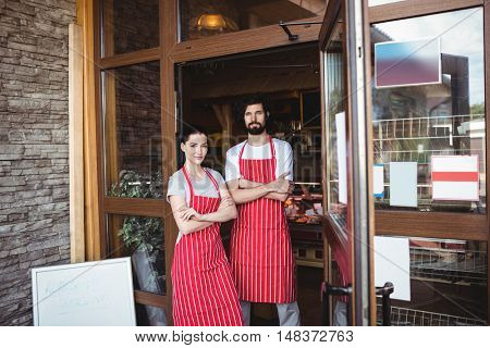 Portrait of couple standing with arms crossed at the entrance of bakery shop