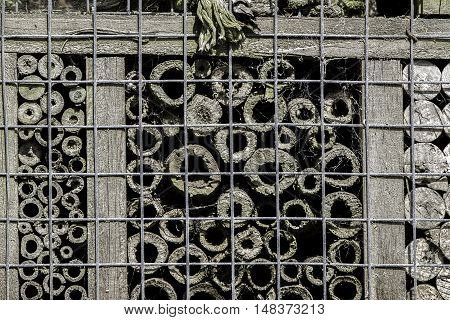 Bug hotel made of various caged tubes. Abstract pattern of concentric circles.