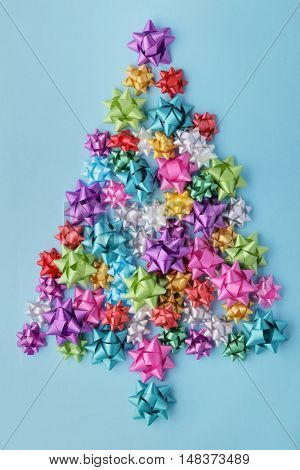 Christmas tree of colorful bows on blue background