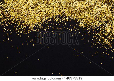 Gold glitter shimmery heading. Invitation card or flyer with sparkling top on black background.