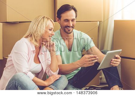 Beautiful mature couple in casual clothes is using a tablet and smiling while sitting on the floor among boxes moving to the new apartment