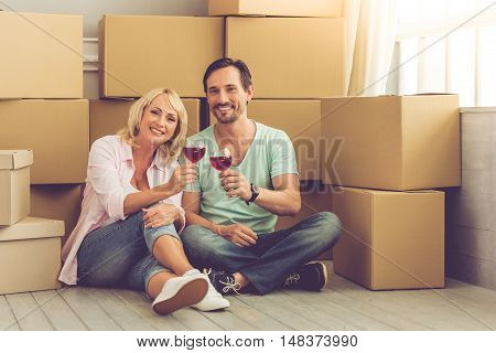 Beautiful mature couple in casual clothes is clanging glasses of wine looking at camera and smiling while sitting on the floor among boxes for move