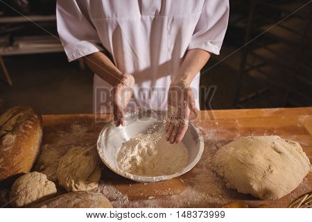 Mid-section of female baker spreading flour in a bowl in bakery shop