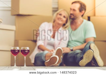 Glasses of wine in the foreground. Happy mature couple is sitting among boxes while moving to the new apartment