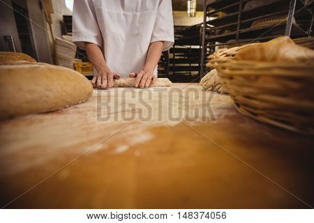 Mid-section of female baker kneading a dough in bakery shop