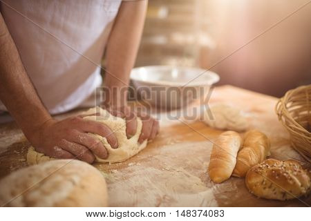 Mid-section of baker kneading a dough in bakery shop