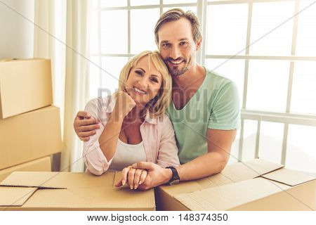 Beautiful mature couple in casual clothes is leaning on the boxes looking at camera and smiling while moving to the new apartment