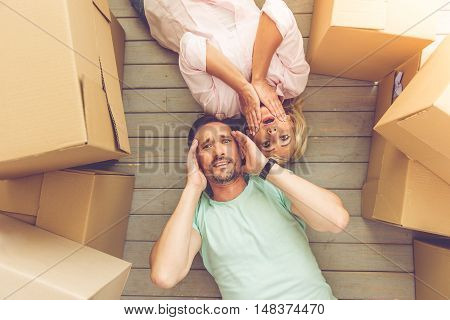 Top view of beautiful mature couple in casual clothes looking at camera touching their faces and showing confusion while lying on the floor among boxes for move
