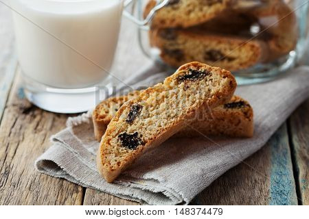 Biscotti or cantucci with raisins and milk on wooden rustic table. Traditional Italian biscuit or cookie.