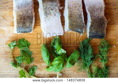 Raw zander fish fillets with various herbs against a wooden cutting board.