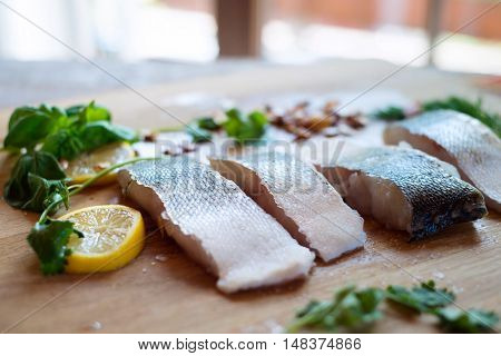 Raw zander fish fillets with lemon slices and herbs on a wooden cutting board.