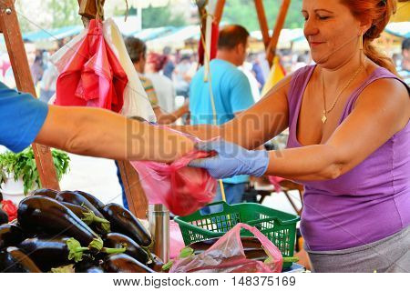 CLUJ-NAPOCA ROMANIA - SEPTEMBER 17 2016: Unidentified farmer woman holds plastic bag while buyer fills it with vegetables at the market.