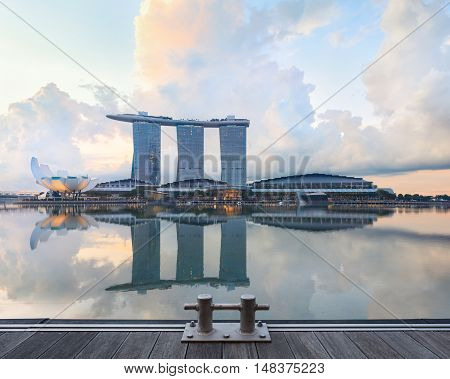 Singapore central quay with wooden pier and bollard on foreground. Modern city architecture at sunrise
