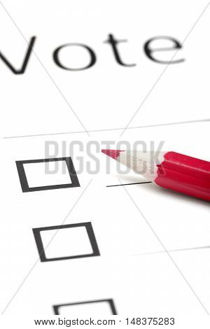 Voting bulletin with red pencil. Close-up photo with shallow depth of field