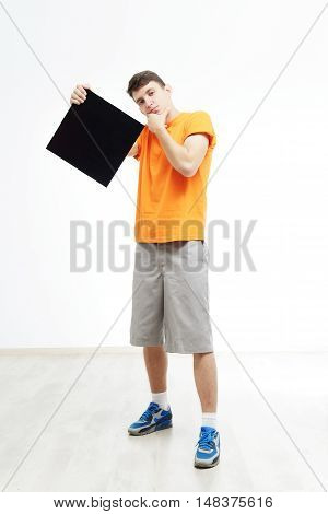 Young man with sign he is holding against a white background. Young rapper is holding a sign. Dancer is wearing in orange T-shirts with sign in a hand. Hip-hop dancer advertise something