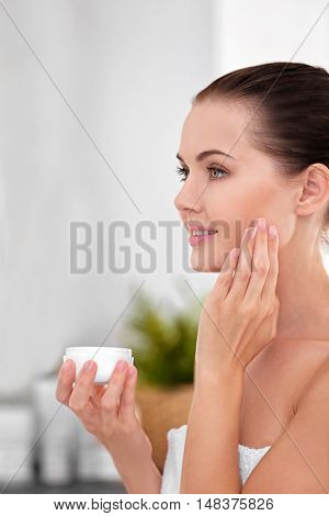 Portrait of beautiful young woman in white towel applying cream onto face