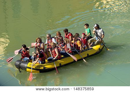 VERONA ITALY - SEPTEMBER 17 2016: Tocati International festival of street games. Rafting a group of people with an instructor on an inflatable boat in the city of Verona on the Adige river near Ponte Pietra
