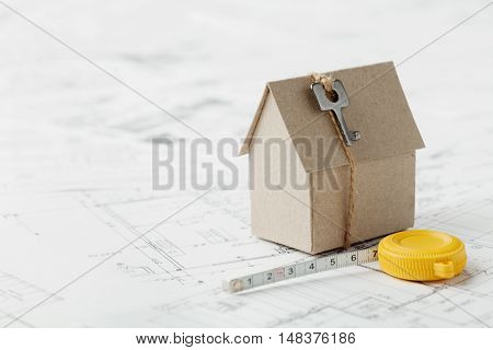 Model of cardboard house with key and tape measure on blueprint. Home building, architectural and construction design concept.