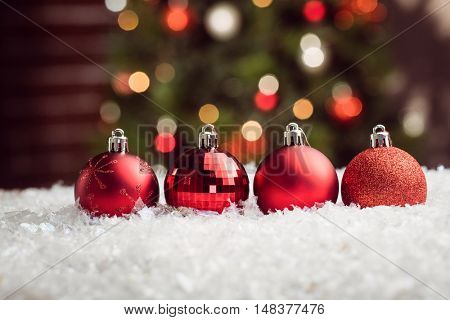 Composite image of Christmas baubles lined up against christmas tree background