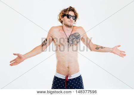 Portrait of curly unshure confused beach man shrugging shoulders isolated over white background