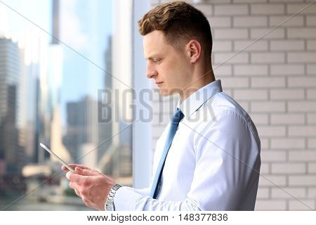 Businessman working with digital tablet. Downtown background behind