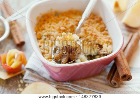 Apple crumble with cinnamon on rustic wooden table. Delicious french autumn or winter dessert for holidays. Macro.