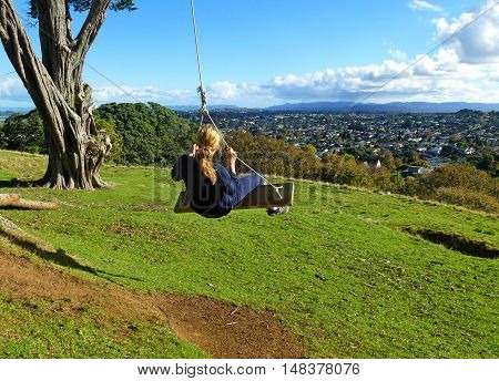 Young blonde woman on the swing looking at the city of Auckland, New Zealand