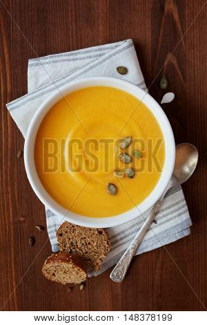 Fresh autumn pumpkin cream soup in white bowl, dietary vegetable soup. Top view.
