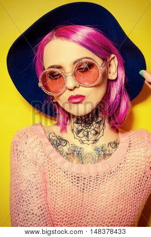 Party girl with crimson hair wearing bright clothes and sunglasses over yellow background. Bright style, fashion. Optics style. Tattoo.