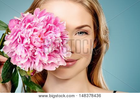 Smiling young woman with natural make-up and beautiful blonde hair holding a peony flower. Beauty, fashion, cosmetics.
