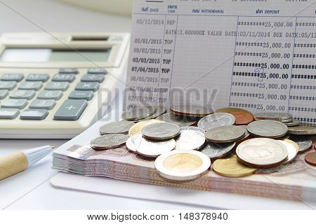 Concept of savings : Coins and Thai Baht money on savings account passbook, calculator and pen
