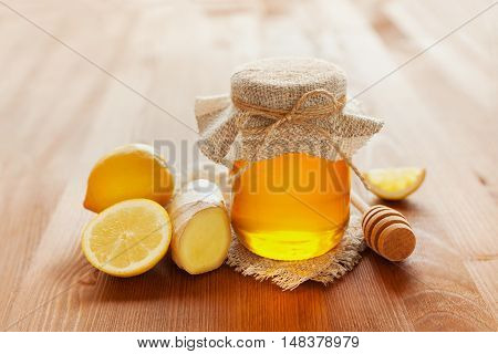 Natural honey in a pot or jar with twine tied in a bow, dipper, lemon and ginger on a wooden background.