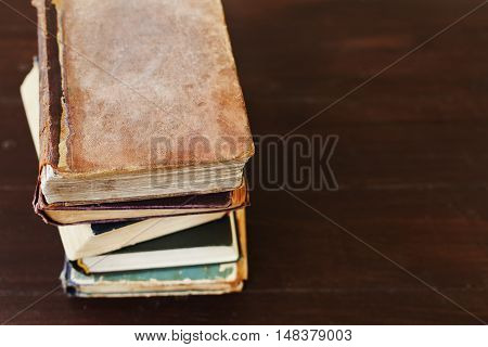 Stack of old vintage books on brown wooden background, selective focus. Copy space for text.