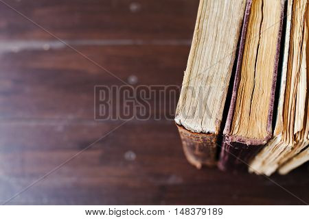 Old vintage books on dark wood background, selective focus and shallow dof. Copy space for text.