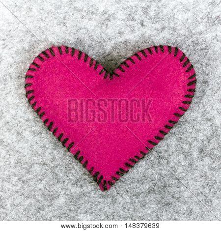 pink felt heart on a gray background