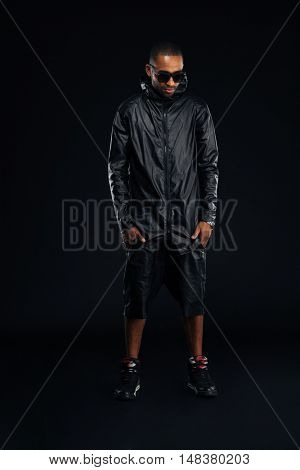 Attractive afro american man in trendy cloth posing with hands in pockets over black background