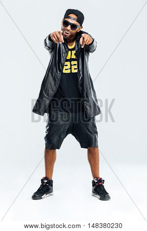 Smiling happy african man in stylish clothes pointing fingers at camera over white background