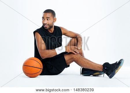 Happy young man basketball player sitting and looking away over white background