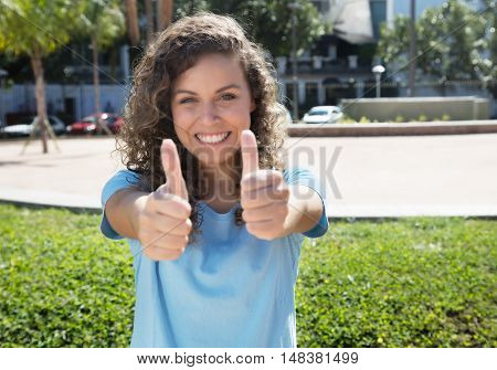 North american woman with curly hair showing both thumbs in the city in the summer