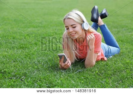Young beautiful woman with headphones lying on the grass and listening to music