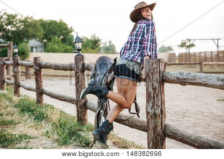 Full length of a happy cowgirl in hat posing at fence at ranch
