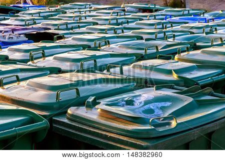 Many green plastic refuse wheelie bins lined up outside for tourists