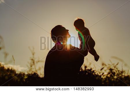 Father and little newborn daughter silhouettes at sunset sky
