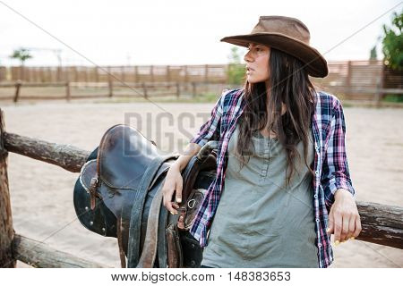 Young cute cowgirl leaning on the ranch fence and looking away