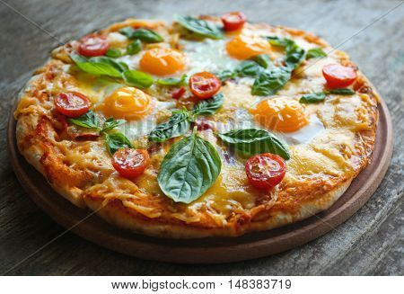 Margarita pizza with basil leaves and egg on wooden background
